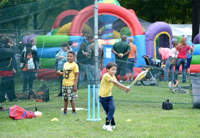 A kid try cricket at the HarvestFest.