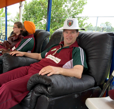 NVCC vice captain Bernie Peacock takes a well-deserved rest after his haul of 3 wickets for 25 runs in 5.5 overs. Also pictured is NVCC member Chandanpreet Virk and his wife Michelle. Top photo, team picture with Bradshaw CC left (yellow and green) and NVCC on right (maroon and green).