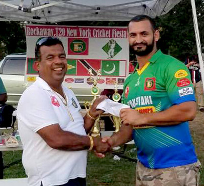 Abdullah Syed, MVP of the final (right), collects his check for the nine sixes he struck which earned him $180.00.