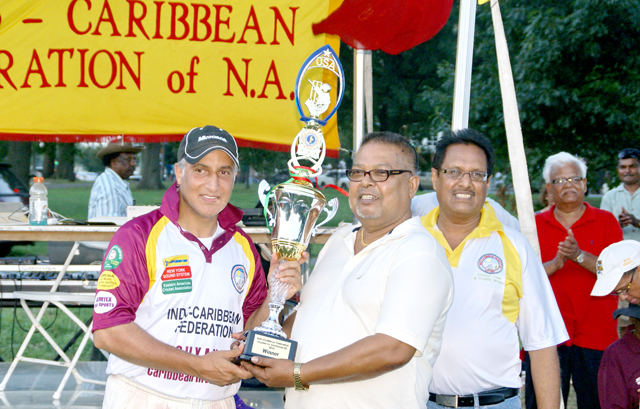 Amjad Khan, captain of the Caribbean Invitation XI team receiving the winning trophy from Kawal Narain of Jemtex Sports USA.
