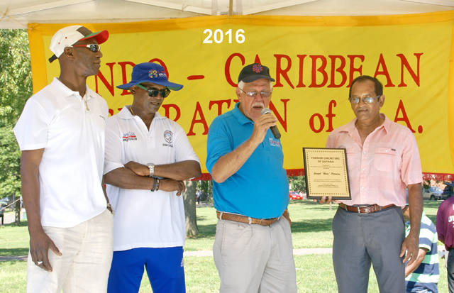 Reds Perriera accepting an award from Former Guyana national players, from left Ray Joseph, Sew Shivnarine and Tyronne Etwaroo.